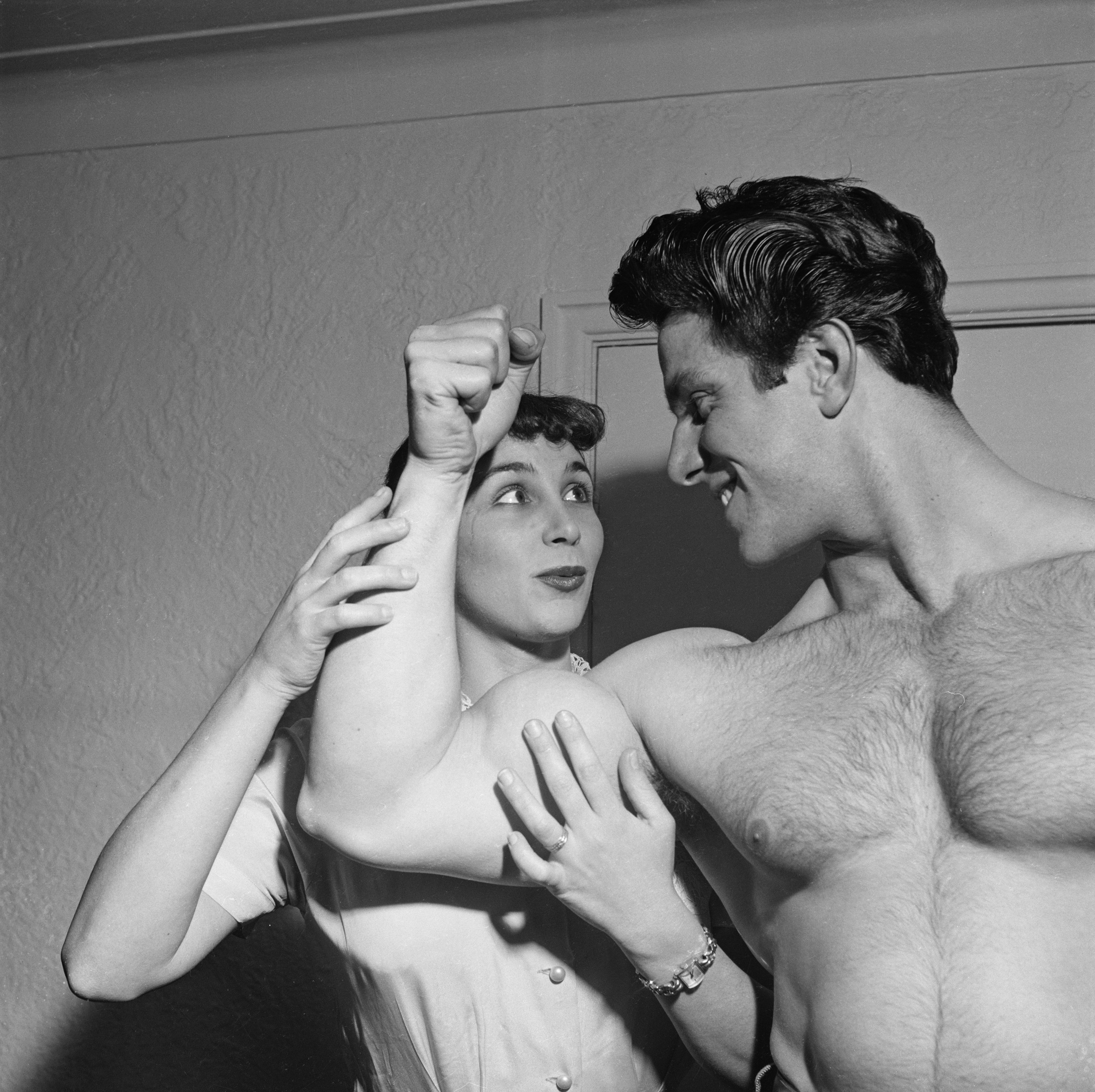 English bodybuilder Reg Park (1928 - 2007) flexes his biceps for the benefit of his wife, South African ballet dancer Mareon Park, circa 1955. Reg Park was the first Englishman to win the Mr Universe title and later went on to act in five Italian Hercules sword-and-sandal films in the early 1960s. Park runs his own businesses, publishing a bodybuilding magazine and supplying weight-training equipment.