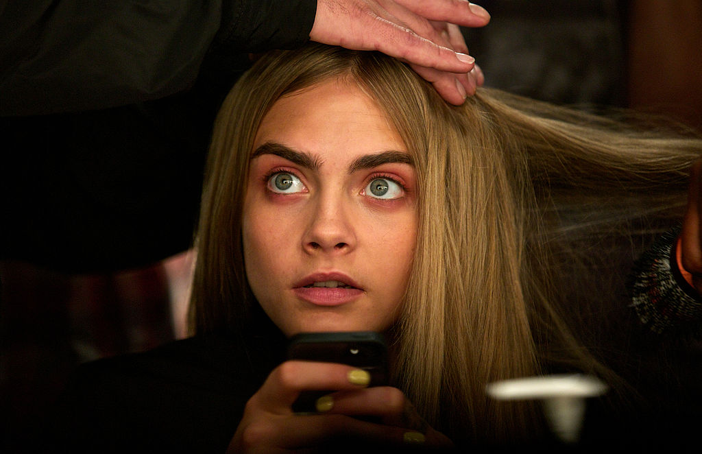 Cara Delevingne gets her hair done backstage ahead of the Burberry Prorsum 2014 Spring/Summer catwalk show during the London Fashion Week in London on September 16, 2013. AFP PHOTO / ANDREW COWIE