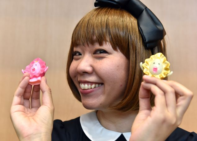 """Japanese artist Megumi Igarashi, who calls herself Rokude Nashiko -- offensive slang which loosely translates as """"reprobate child"""" -- shows small mascots shaped to represent a vagina, at a press conference after the first hearing of her trial in Tokyo on April 15, 2015. Igarashi, who has created genital-inspired artworks and was arrested last December on obscenity charges for distributing 3D scans of her own genitals, plead not guilty during the first hearing of her trial at the Tokyo district court."""