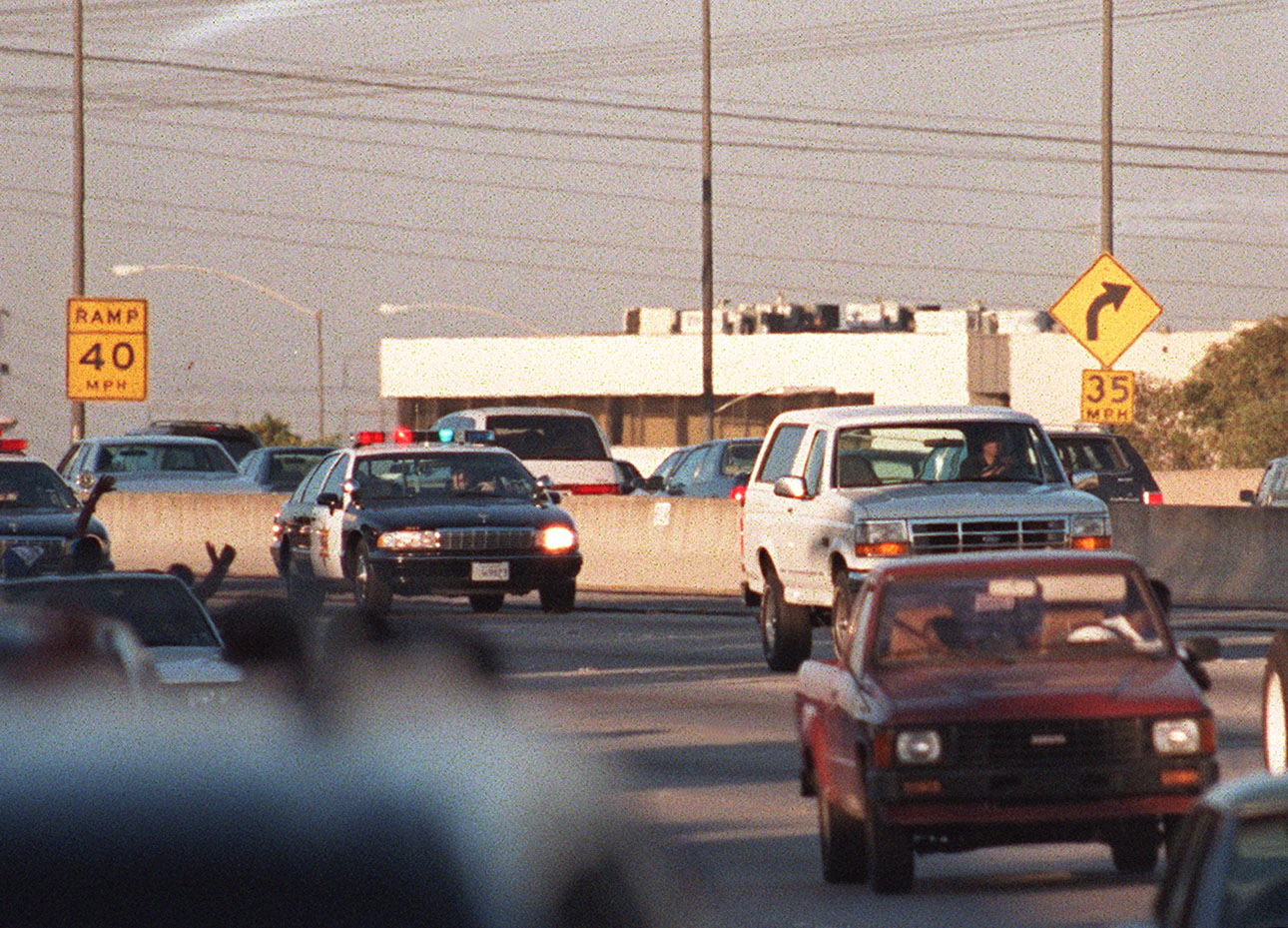 LOS ANGELES - JUNE 17: Motorists wave as police cars pursue the Ford Bronco (white, R) driven by Al Cowlings, carrying fugitive murder suspect O.J. Simpson, on a 90-minute slow-speed car chase June 17, 1994 on the 405 freeway in Los Angeles, California. Simpson's friend Cowlings eventually drove Simpson home, with Simpson ducked under the back passenger seat, to Brentwood where he surrendered after a stand-off with police.