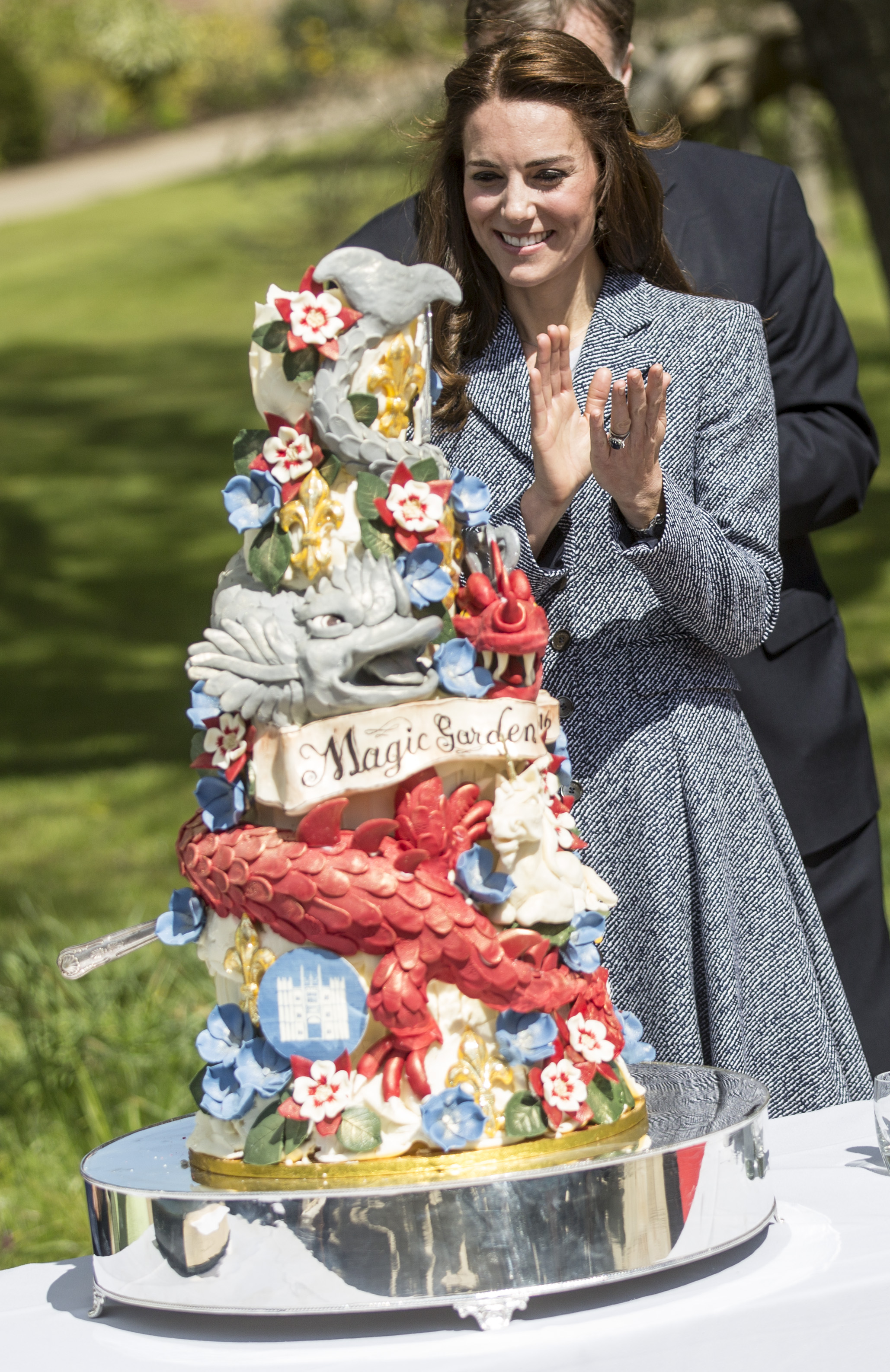 LONDON, ENGLAND - MAY 04: Catherine, Duchess of Cambridge stands next to an ornate cake decorated with dragons and magical creatures baked especially for the opening as she officially opens The Magic Garden at Hampton Court Palace on May 4, 2016 in London, England.