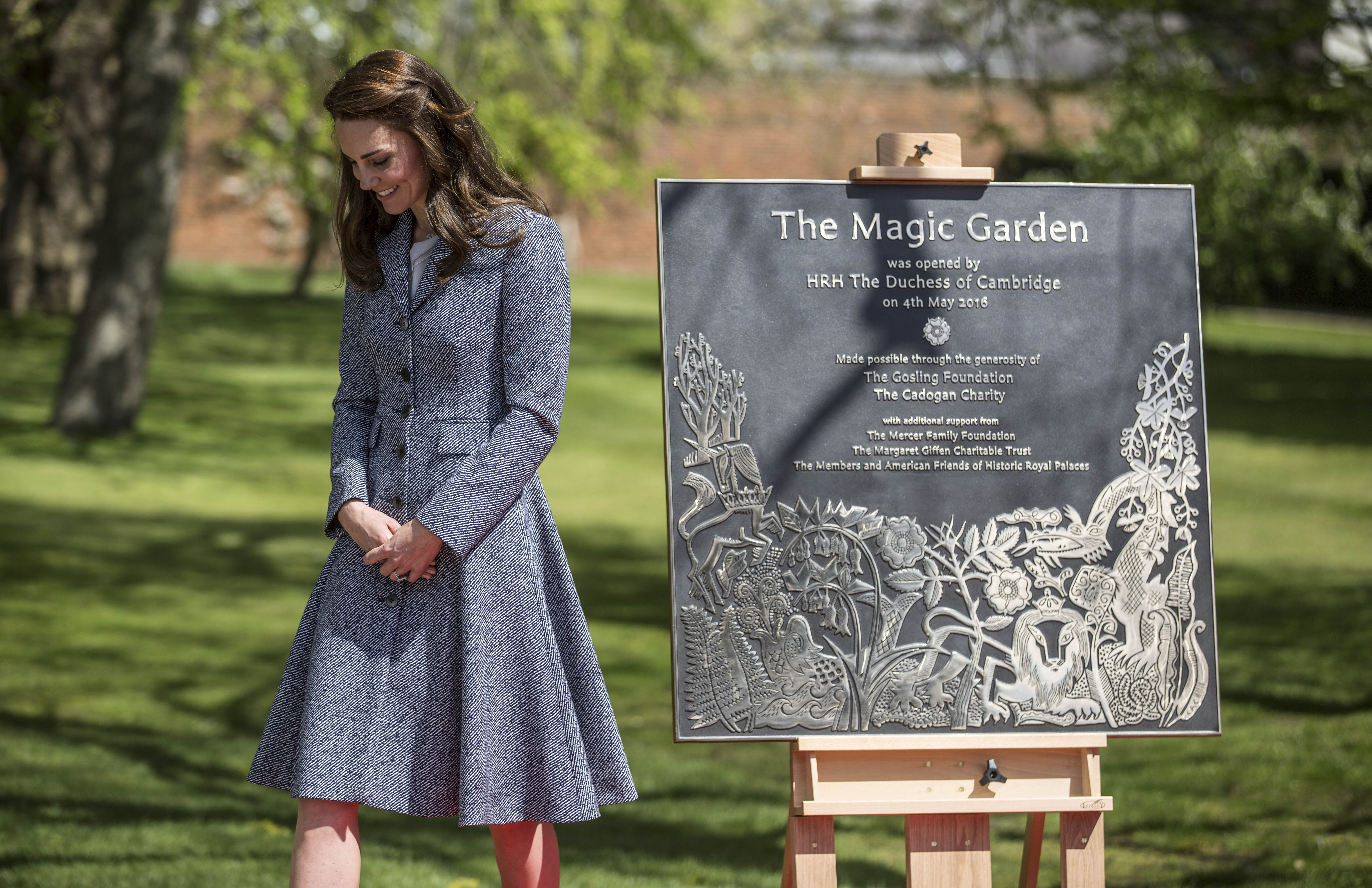 LONDON, ENGLAND - MAY 04: Catherine, Duchess of Cambridge stands with the plaque she unveiled as she officially opens The Magic Garden at Hampton Court Palace on May 4, 2016 in London, England.