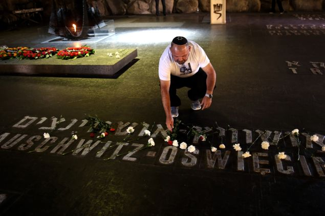 An Israeli relative of Holocaust victims lays a flower at the Hall of Remembrance where the names of major death and concentration camps are written during a ceremony marking the annual Holocaust Remembrance Day at the Yad Vashem Holocaust Memorial in Jerusalem on May 5, 2016.