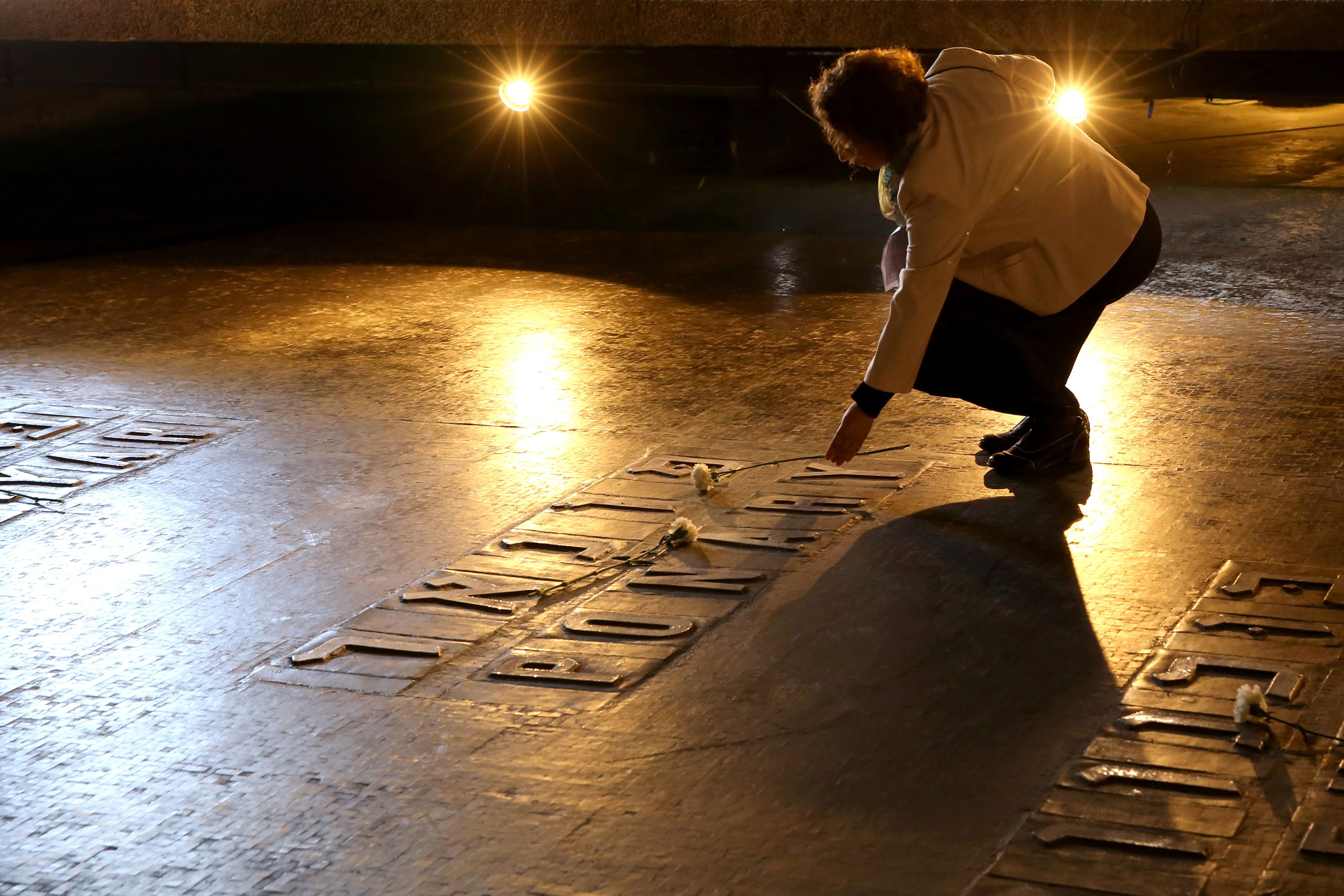 An Israeli relative of Holocaust victims lays a flower at the Hall of Remembrance where the names of major death and concentration camps are written during a ceremony marking the annual Holocaust Remembrance Day at the Yad Vashem Holocaust Memorial in Jerusalem on May 5, 2016. The state of Israel marks the annual Memorial Day commemorating the six million Jews murdered by the Nazis in the Holocaust during World War II. / AFP / GALI TIBBON