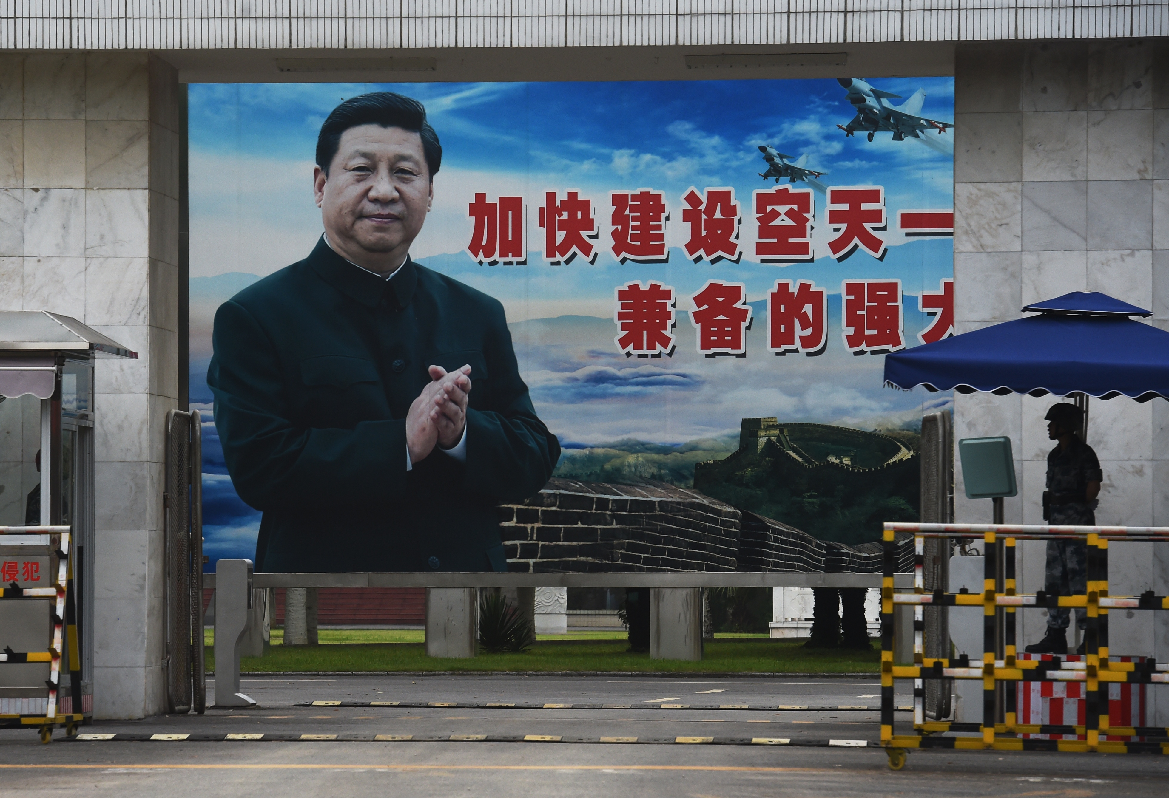"A soldier stands guard in front of a huge portrait of Chinese President Xi Jinping at the entrance to a military base in Guilin, in China's southern Guangxi region on May 13, 2016. The slogan reads ""Speed up the establishment of a powerful people's Air Force and sharpen offensive and defensive capabilities"". / AFP / GREG BAKER"