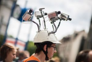 Chairman of Hesse's Pirate Party Volker Berkhout wears a hat with mock surveillance cameras during a demonstration against spying activities of the US intelligence agency NSA and its German partner service BND in Frankfurt am Main, central Germany, on May 30, 2015.
