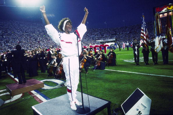 Whitney Houston sings the National Anthem during the pregame show at Super Bowl XXV while tens of thousands of football fans wave tiny American flags in an incredible outburst of patriotism during the Persian Gulf War on 01/27/1991.
