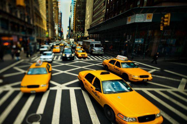 Taxis drive through Manhattan.