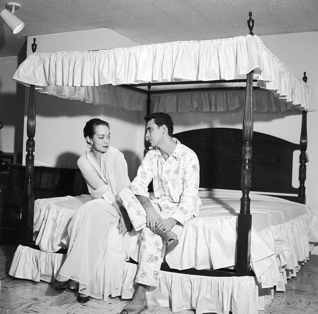 circa 1956: A couple sitting on a specially designed four poster bed. (Photo by Three Lions/Getty Images)