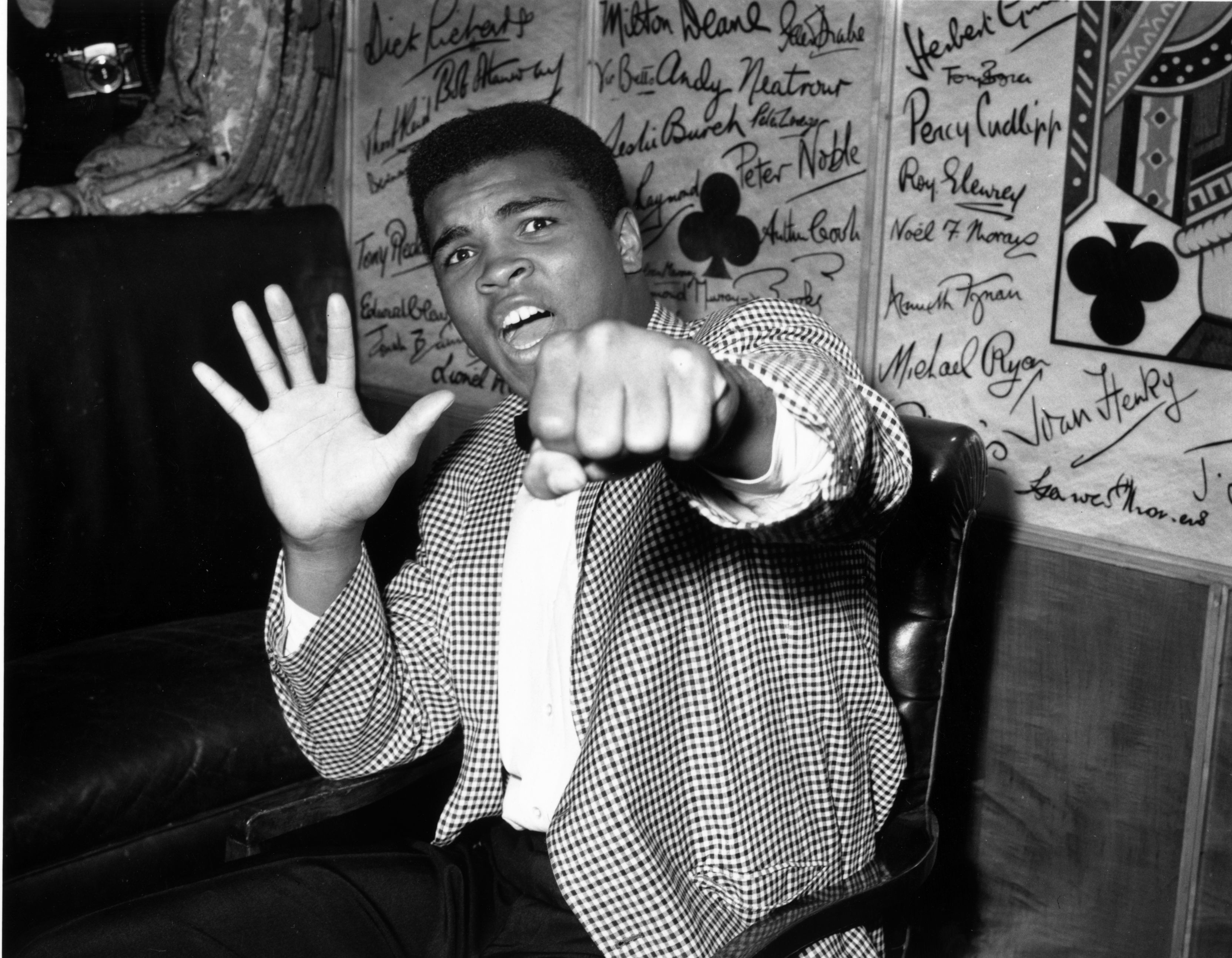 27th May 1963:  Supremely confident American boxer Cassius Clay holds up five fingers in a prediction of how many rounds it will take him to knock out British boxer Henry Cooper.