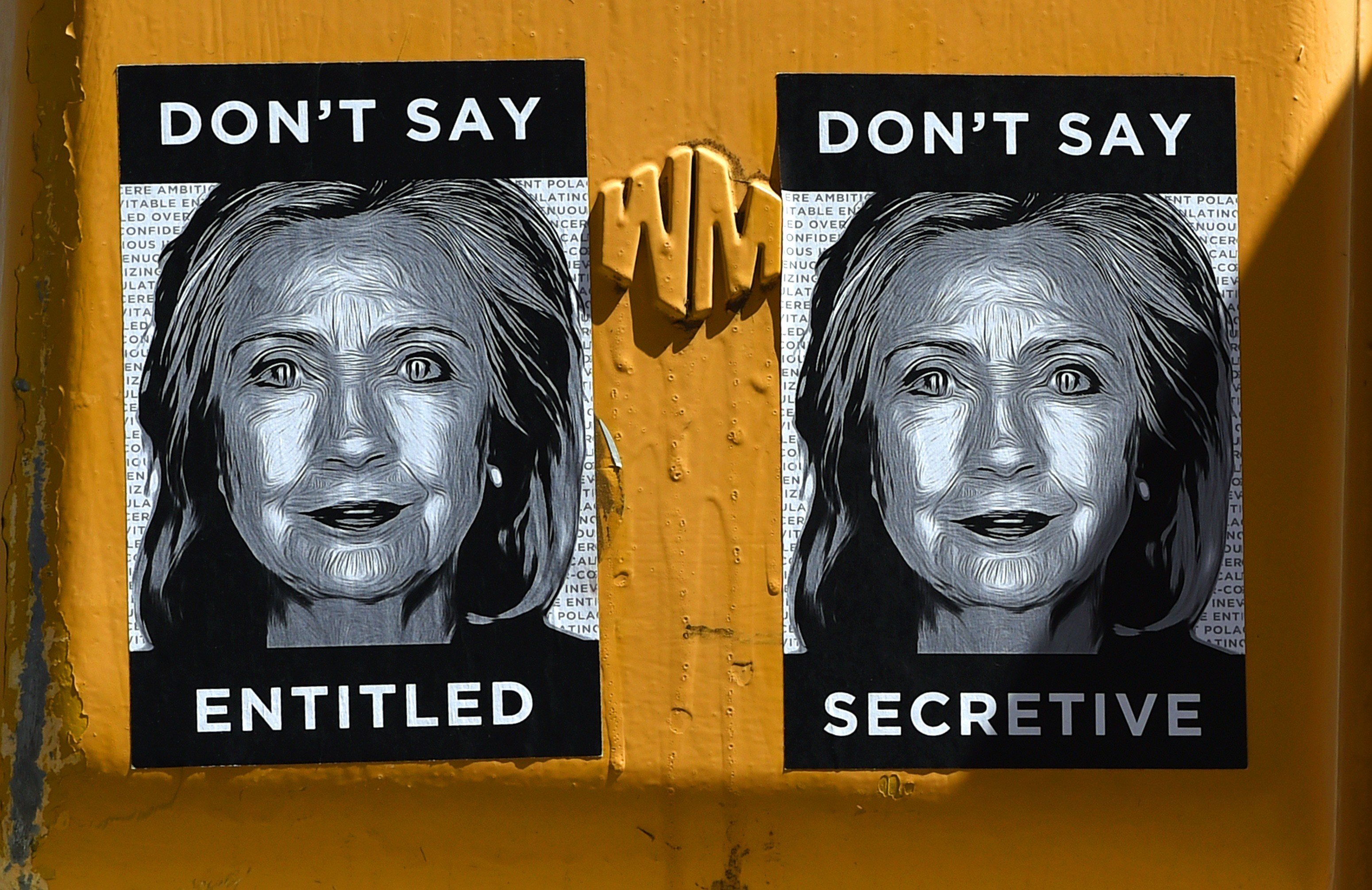 Anti-Hillary Clinton posters are seen on a sign post in Brooklyn on April 16, 2015, just blocks from Clintons new Brooklyn , New York 2016 presidential campaign headquarters . The posters feature illustrations of Clintons face along with slogans, including: Dont Say Secretive and Dont Say Entitled. AFP PHOTO / TIMOTHY A. CLARY