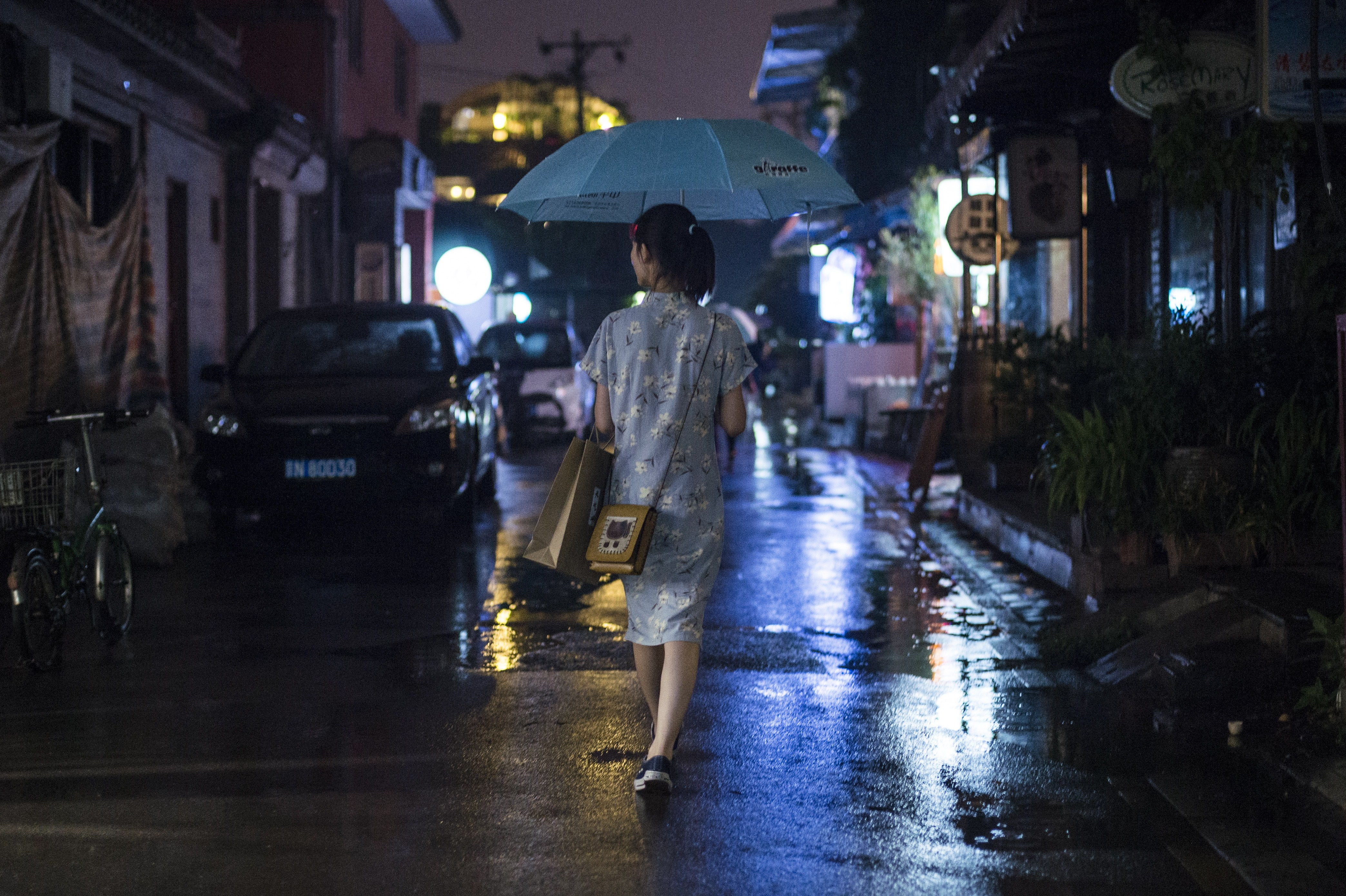 A woman walks under the rain with her umbrella in a hutong in Beijing on June 9, 2015.  AFP PHOTO / FRED DUFOUR