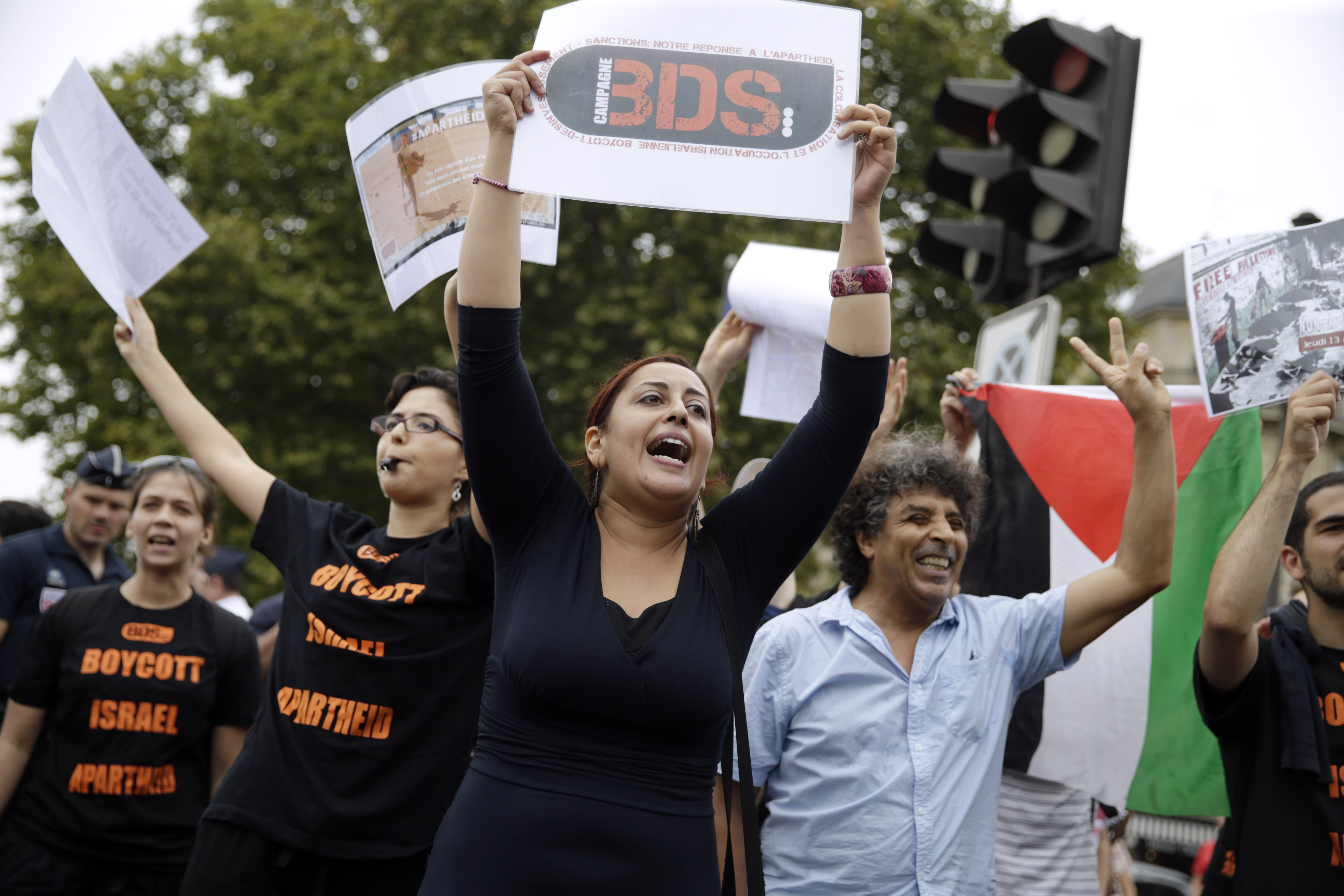 """A Pro-Palestinian """"Gaza Beach"""" protestor holds a placard reading """"BDS (Boycotts, divestment and sanctions) during a gathering on the sidelines of """"Tel Aviv Sur Seine"""", a beach event celebrating Tel Aviv, in central Paris on August 13, 2015. A Paris beach event celebrating Tel Aviv attracted a handful of visitors but a huge number of journalists, riot police and security guards, as well as a much larger """"Gaza Beach"""" protest. Bemused locals who headed down to """"Tel Aviv Sur Seine"""" had to manoeuvre through bag checks, security pat-downs and metal detectors to reach the small stretch of sand on the banks of the Seine. AFP PHOTO / KENZO TRIBOUILLARD"""