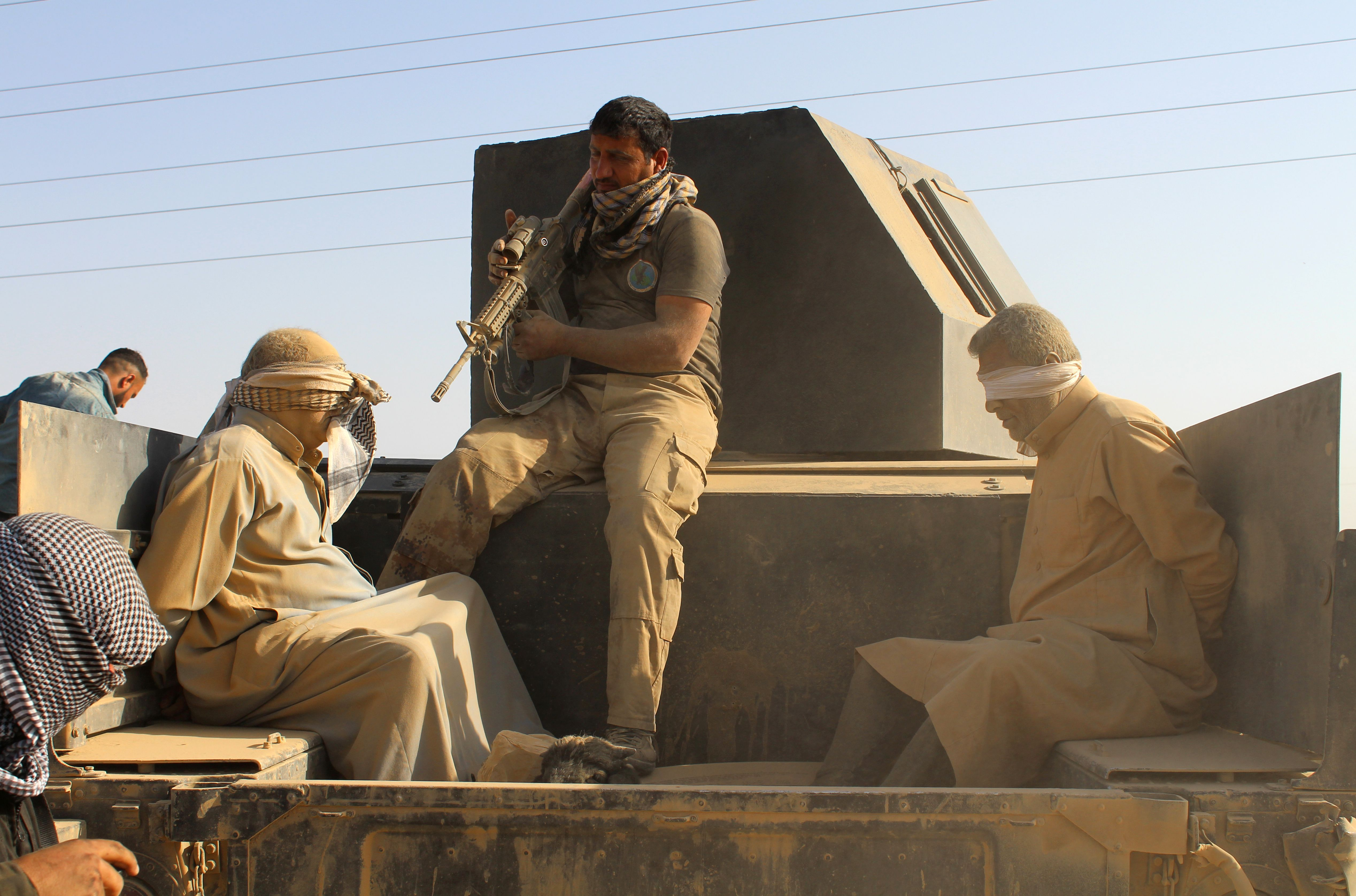 """Iraqi government and counter-terrorism forces arrest men suspected of belonging to the Islamic State (IS) jihadist group on March 10, 2016 following an operation to retake the town of Zankura, northwest of Ramadi, in Anbar province, from IS. Iraqi forces retook a town from the Islamic State jihadist group in Anbar province Thursday and evacuated 10,000 civilians as they advanced up the Euphrates valley, a security spokesman said. The sprawling province of Anbar -- which borders Syria, Jordan and Saudi Arabia -- was at the heart of the """"caliphate"""" that IS proclaimed in 2014. The jihadist group still holds most of the province but the noose is tightening around some of its key bastions. / AFP / MOADH AL-DULAIMI"""