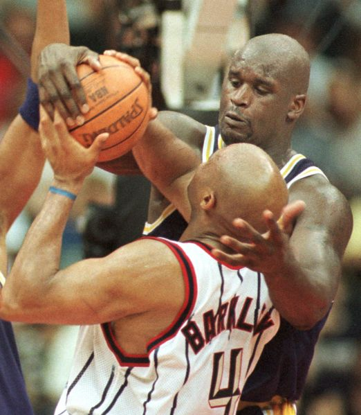 Shaquille O'Neal of the Los Angeles Lakers (back) stuffs Charles Barkley of the Houston Rockets during late action at Compaq Center 1 May 1999 in Houston, Texas.