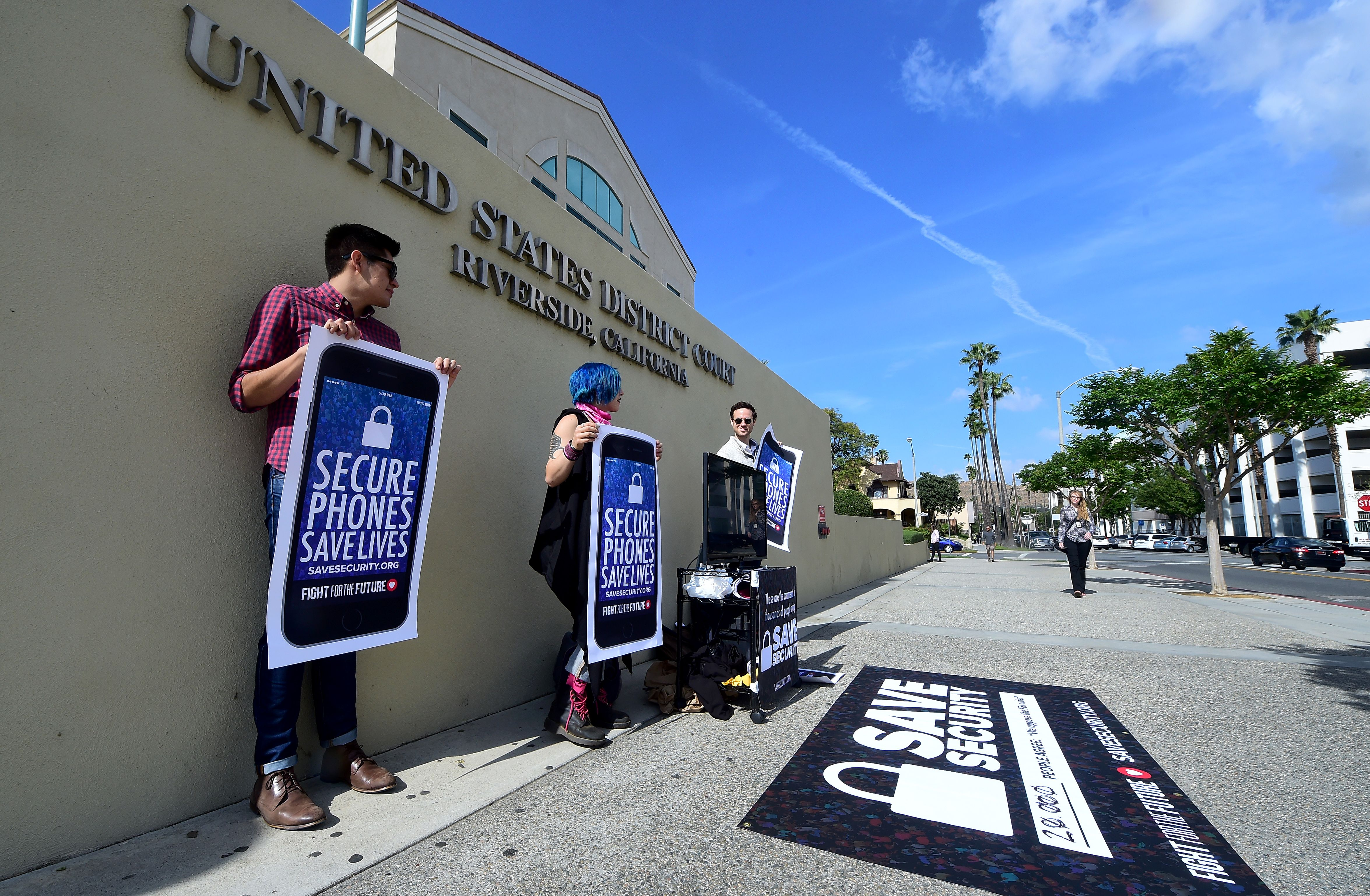 "Activists Luis Nolasco (L), Aki Rose (C) and Josh Rabb (R) hold placards reading ""Secure Phones Saves Lives"" during a protest in front of the US District Court in Riverside, California, on March 22, 2016. The US government's decision to delay its effort to force Apple to help unlock an attacker's iPhone may only postpone the inevitable drawn-out battle over encryption and data protection. / AFP / FREDERIC J. BROWN (Photo credit should read FREDERIC J. BROWN/AFP/Getty Images)"