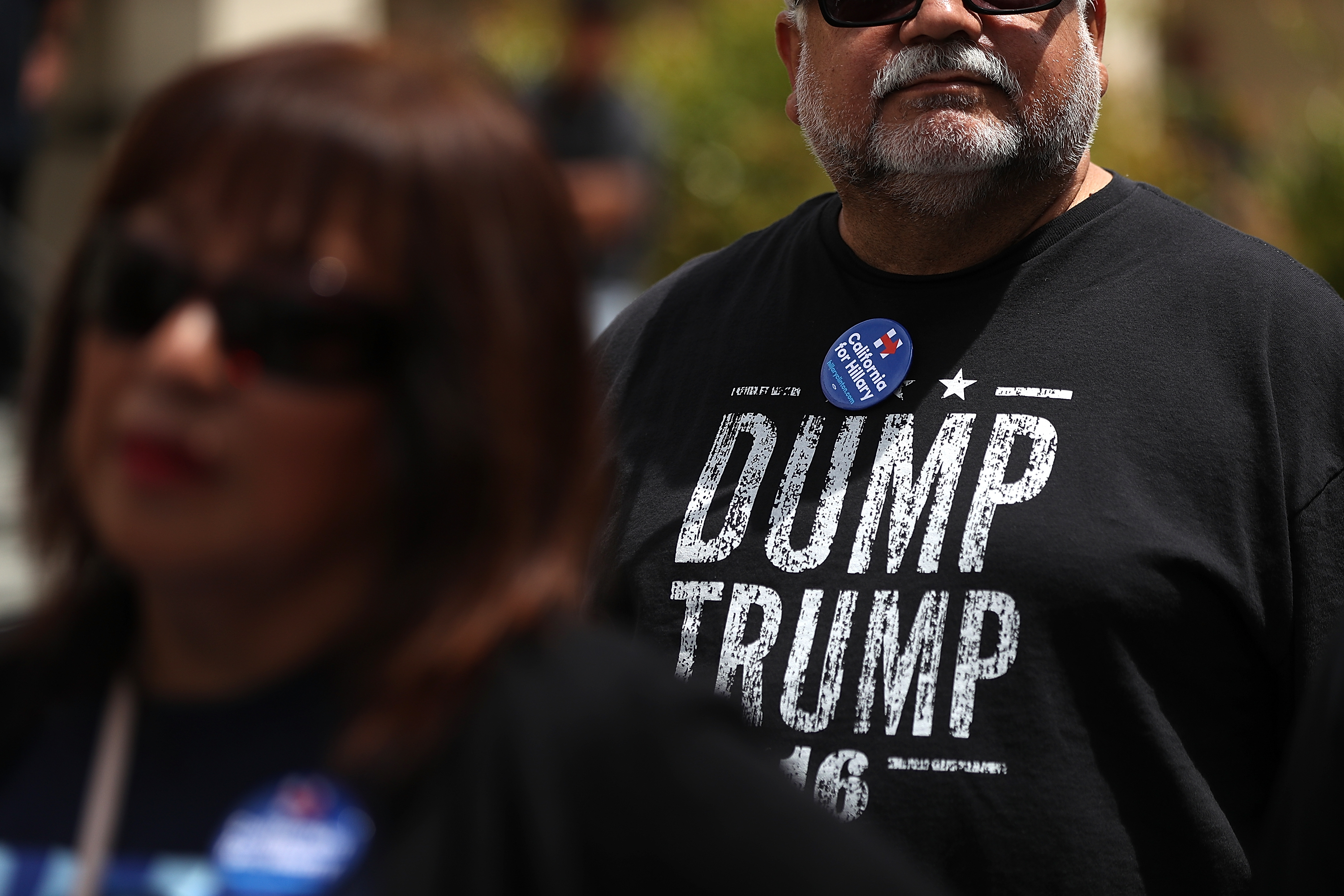 "SALINAS, CA - MAY 25:  A supporter of democratic presidential candidate former Secretary of State Hillary Clinton wears a ""Dump Trump"" shirt before a campaign rally at Harrell College on May 25, 2016 in Riverside, California. Hillary Clinton is campaigning in California ahaed of the State's presidential primary on June 7th."