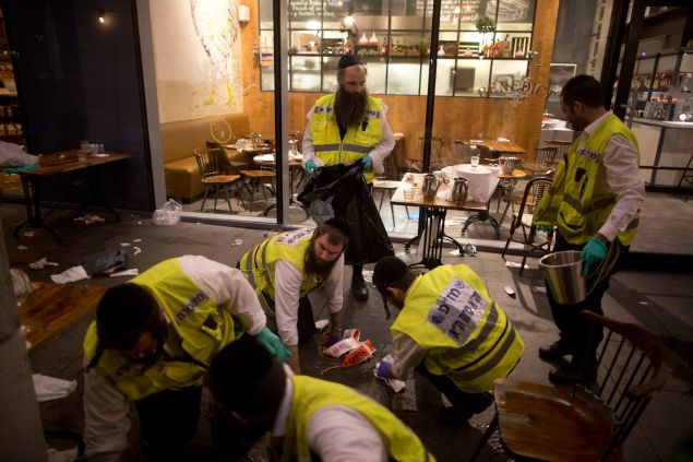 Members of an Israeli ZAKA - Identification, Extraction and Rescue team work at the scene of a shooting outside Max Brenner restaurant in Sarona Market on June 8, 2016 in Tel Aviv, Israel.