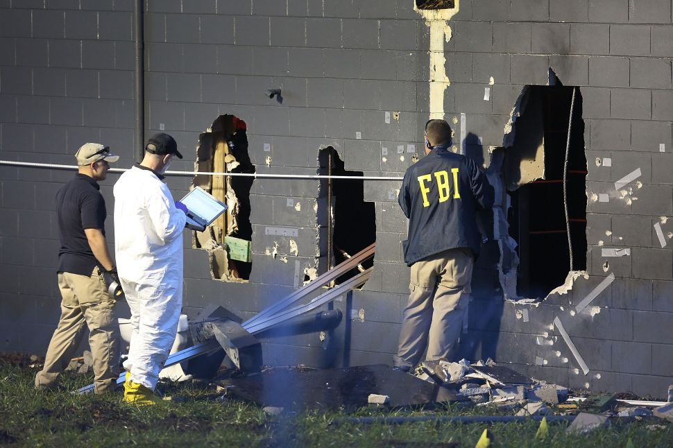 FBI agents investigate near the damaged rear wall of the Pulse Nightclub where Omar Mateen allegedly killed dozens on June 12, 2016 in Orlando, Florida.