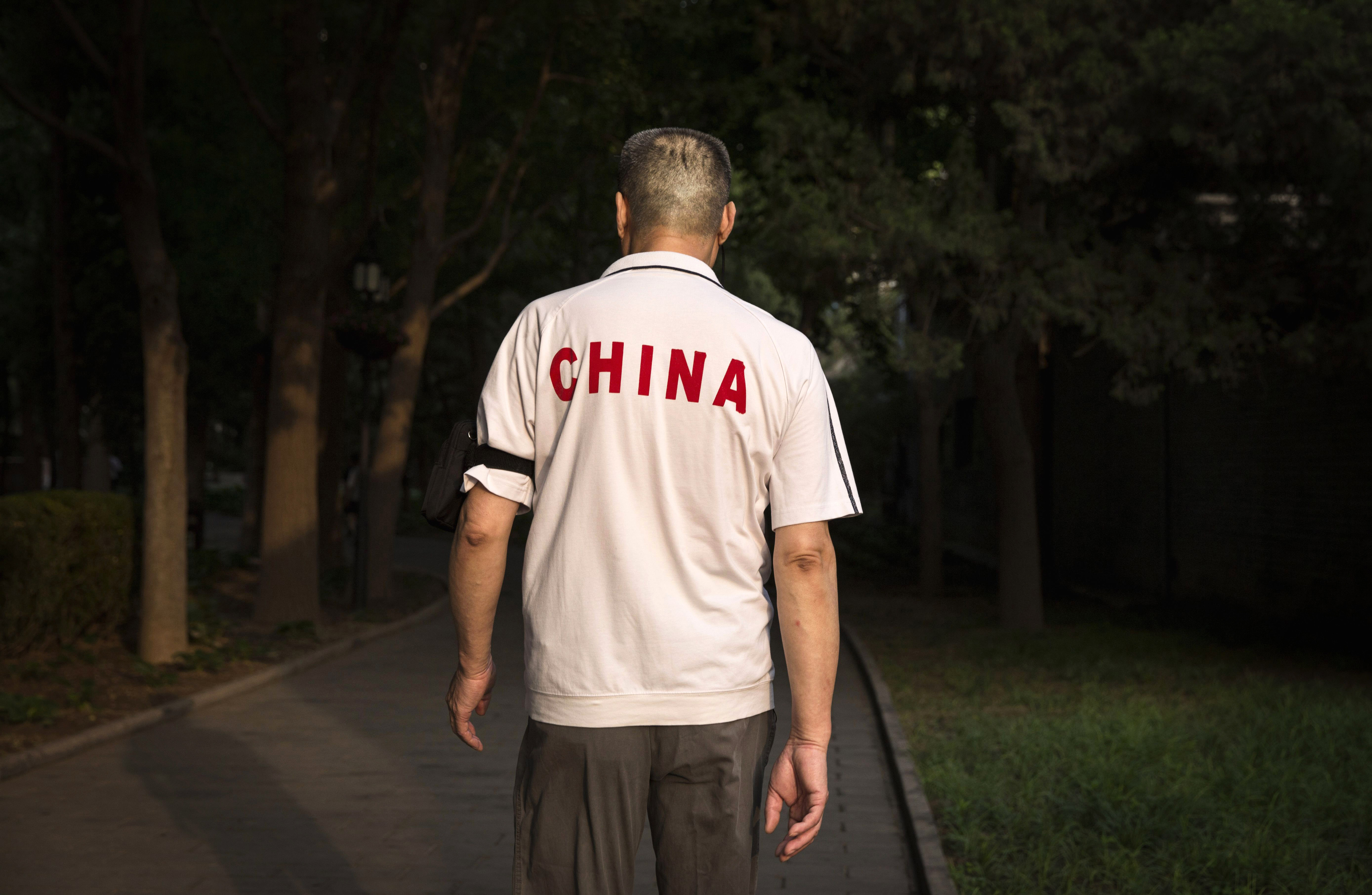 BEIJING, CHINA - JUNE 11: A Chinese man walks at Ritan Park on June 11, 2016 in Beijing, China. Ritan, meaning 'sun altar', is among the oldest parks in Beijing, built in the early 1500s during the Ming dynasty for the emperor to make sacrifices to the sun. Less than half a kilometer square, Ritan these days is considered an oasis of green space in a sprawling city of skyscrapers, notorious air pollution, and a population of over 20 million people. Most Chinese live in small apartments with no access to gardens, leaving parks as a welcome haven for people, especially the elderly, to exercise, socialize, or enjoy a degree of privacy. The average day at Ritan is a showcase of conventional routines such as jogging, dancing, and martial arts, mixed with the assortment of odd activities -- including 'voice exercises' and back-scratching on trees -- that are known to be unique staples of Beijing park life.