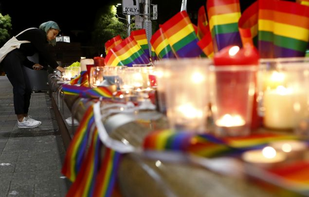 A woman lights a candle during a candlelight vigil for the victims of the Pulse Nightclub shooting in Orlando, Florida, at Oxford St on June 13, 2016 in Sydney, Australia.