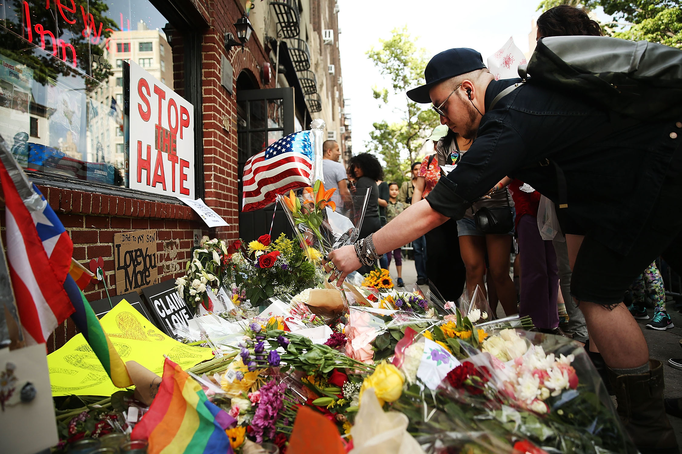 People pause in front of The Stonewall Inn to lay flowers and grieve for those killed in Orlando.