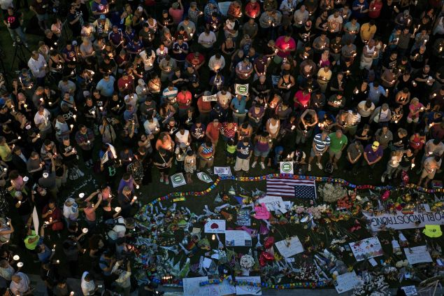 Mourners hold candles while observing a moment of silence during a vigil outside the Dr. Phillips Center for the Performing Arts for the mass shooting victims at the Pulse nightclub June 13, 2016 in Orlando, Florida.