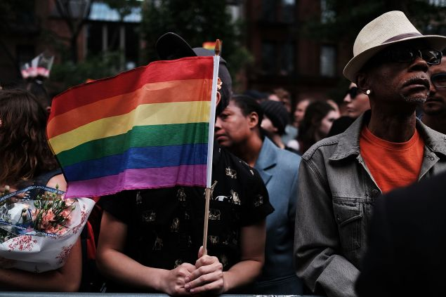 Hundreds of people listen to speakers at a memorial gathering for those killed in Orlando in front of the iconic New York City gay and lesbian bar The Stonewall Inn on June 13, 2016 in New York City. An American-born man who had recently pledged allegiance to ISIS killed 50 people early Sunday at a gay nightclub in Orlando, Florida.