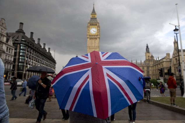 TOPSHOT - A pedestrian shelters from the rain beneath a Union flag themed umbrella as they walk near the Big Ben clock face and the Elizabeth Tower at the Houses of Parliament in central London on June 25, 2016, following the pro-Brexit result of the UK's EU referendum vote. The result of Britain's June 23 referendum vote to leave the European Union (EU) has pitted parents against children, cities against rural areas, north against south and university graduates against those with fewer qualifications. London, Scotland and Northern Ireland voted to remain in the EU but Wales and large swathes of England, particularly former industrial hubs in the north with many disaffected workers, backed a Brexit.