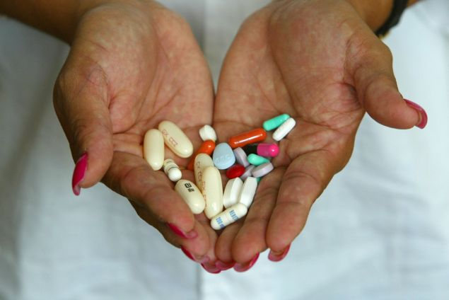Alba Cerrato displays her cocktail of 14 different AIDS medications that she takes three times a day July 11, 2002 in Miami, Florida.