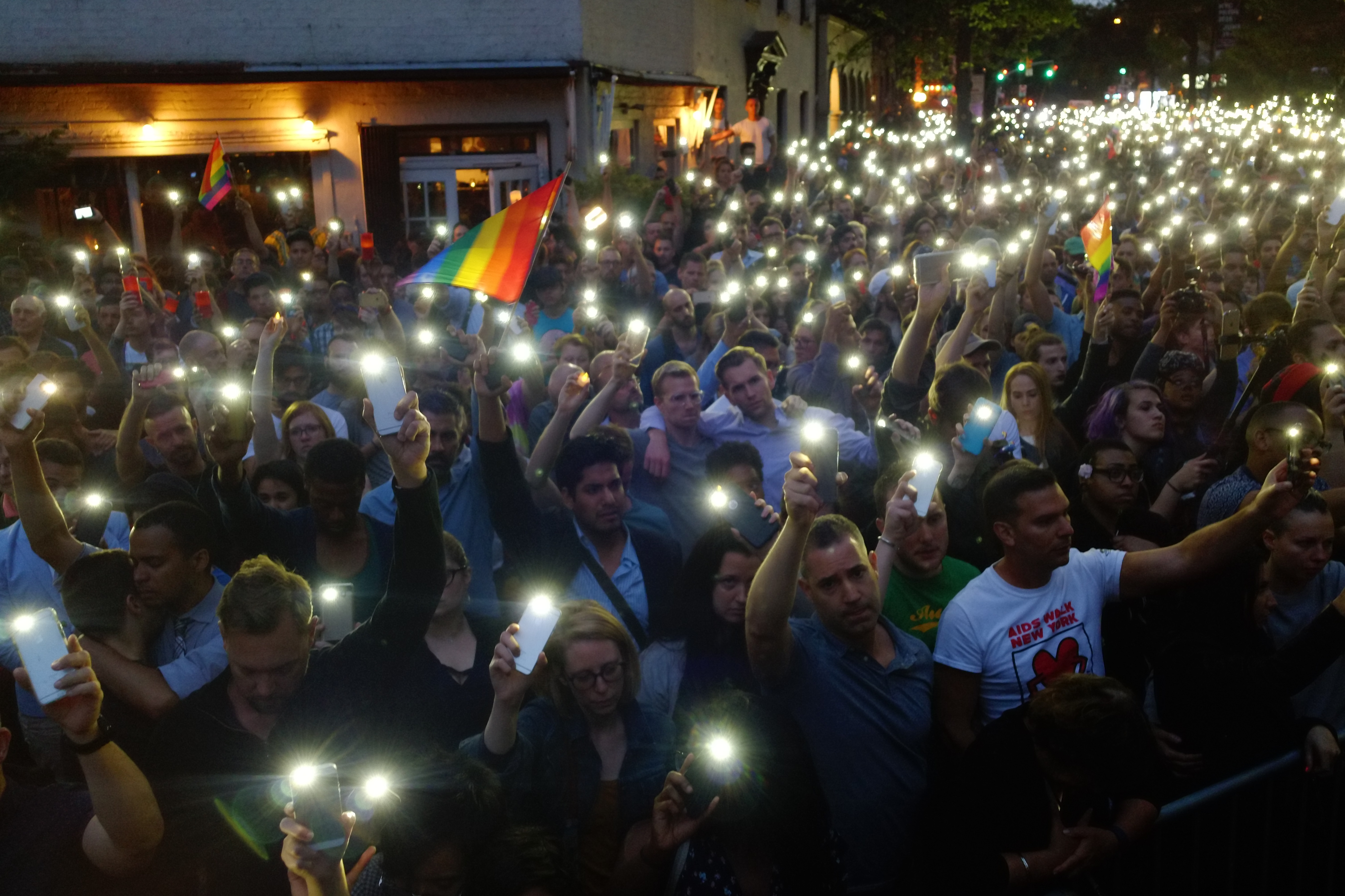 As the names of people killed at the Pulse nightclub were read outside the Stonewall Inn, people hold lights in honor of the victims.