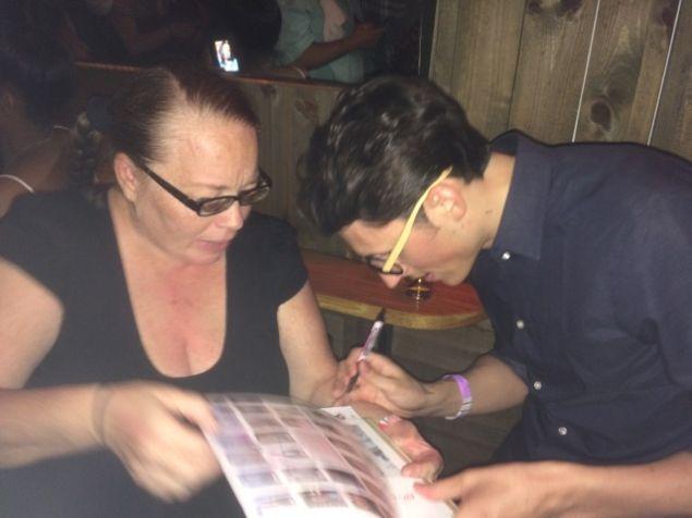 Signing autographs.