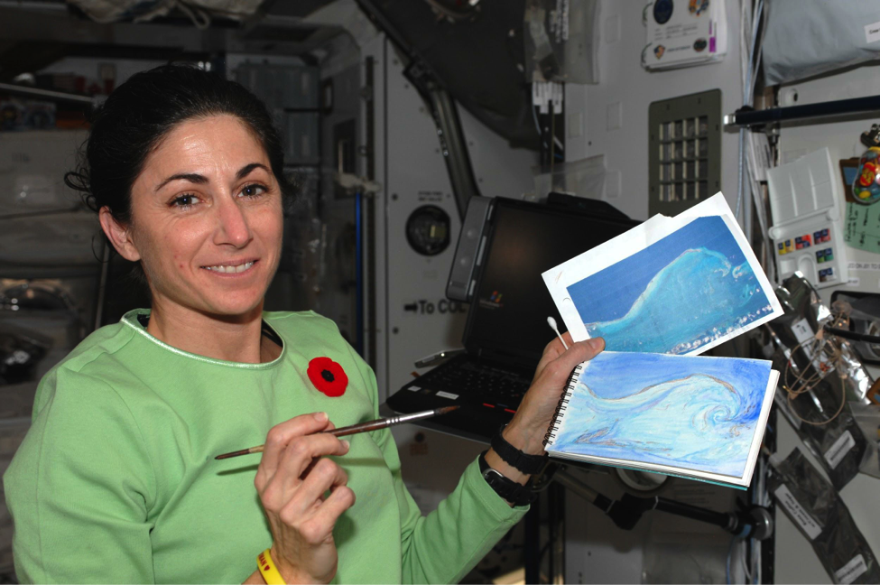 Nicole Stott holding the first painting ever completed in space