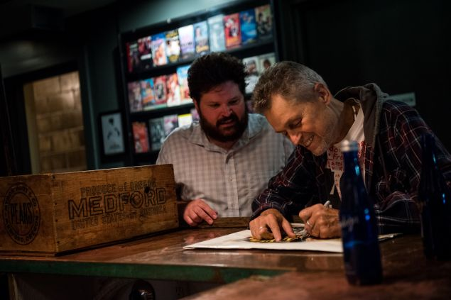 """Director Jonathan Demme signs memorabilia under the watchful eye of Nitehawk technical director and programmer Max Cavanaugh at a recent 35mm screening of Demme's """"Caged Heat"""""""
