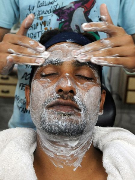 A man indulges in a facial massage at a beauty salon