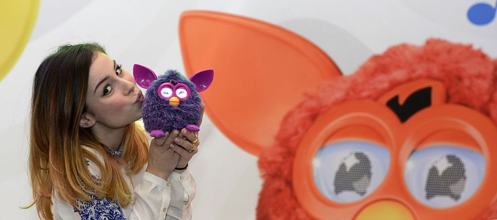 German singer Lena Meyer-Landrut poses with the second version of Hasbo's Furby, in 2013.