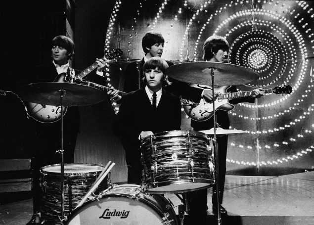 The Beatles perform live on stage in front of a circular lit backdrop at the BBC TV Centre, June 1966.