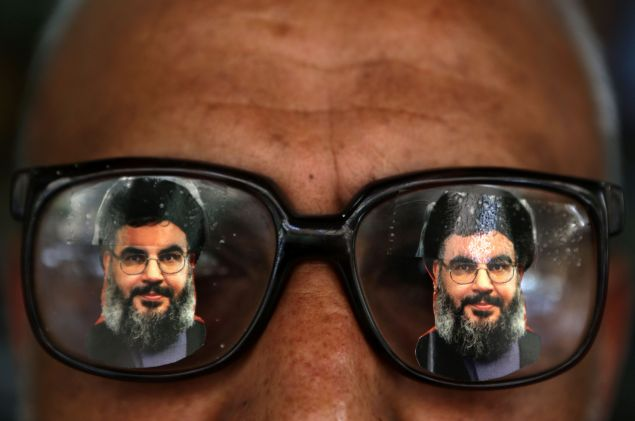 A souvenir shop owner displays glasses decorated with pictures of Hassan Nasrallah, the head of Lebanon's powerful Shiite militant group Hezbollah, in Beirut southern suburb on May 12, 2016.