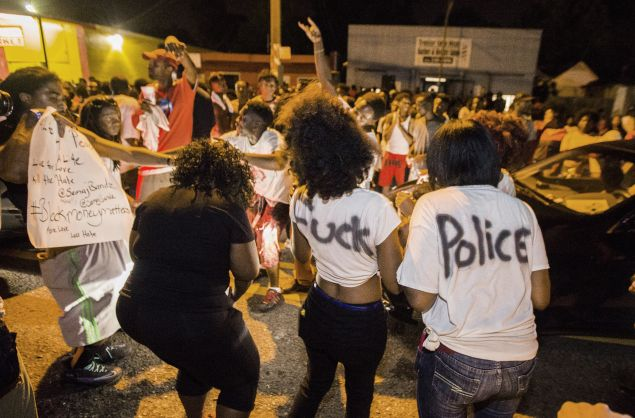Protesters dance in the street near the convenience store where Alton Sterling was shot and killed.