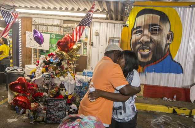 Sandra Sterling (R), Alton Sterling's aunt, visits his memorial at the store where Alton Sterling was killed.