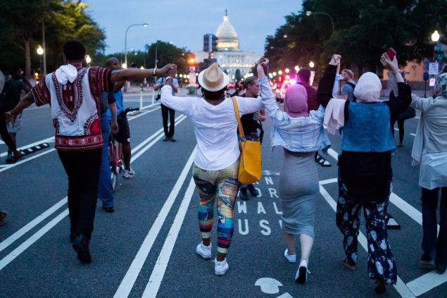 Demonstrators hold hands as they march from The White House to Capitol Hill.