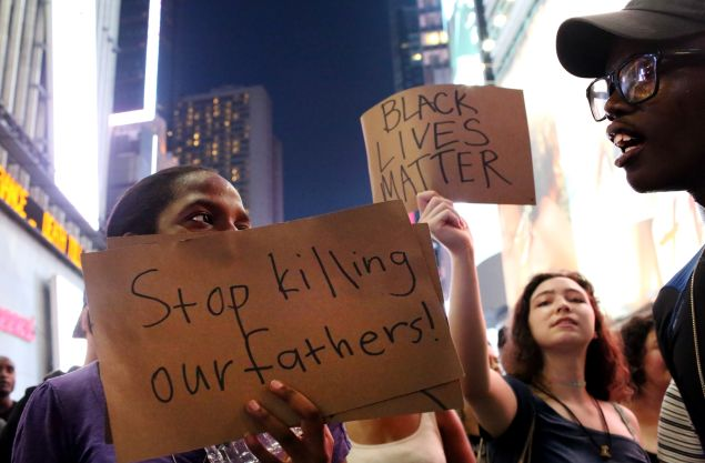 Activists hold signs in Times Square as they protest the recent fatal shootings of two black men by police.