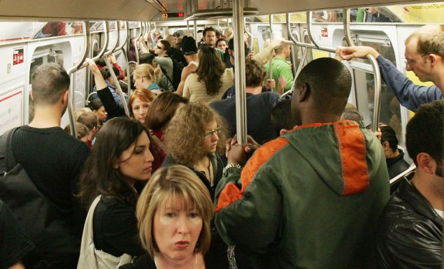 Subway passengers ride a crowded L train.