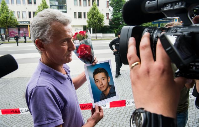 MUNICH, GERMANY - JULY 23: The father of one of the victims is showing flowers and a picture of his son (on the picture his son is named as Zabergja Dijamant) as he arrives outside the OEZ shopping center the day after a shooting spree left nine victims dead on July 23, 2016 in Munich, Germany. According to police an 18-year-old German man of Iranian descent shot nine people dead and wounded at least 16 before he shot himself in a nearby park. For hours during the spree and the following manhunt the city lay paralyzed as police ordered people to stay off the streets. Original reports of up to three attackers seem to have been unfounded. The shooter's motive is so far unclear.
