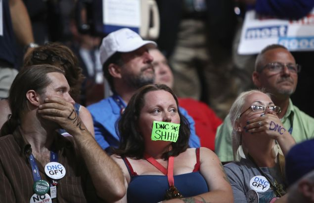 Sanders supporters cover their mouths during roll call on the second day of the Democratic National Convention at the Wells Fargo Center, July 26, 2016 in Philadelphia.