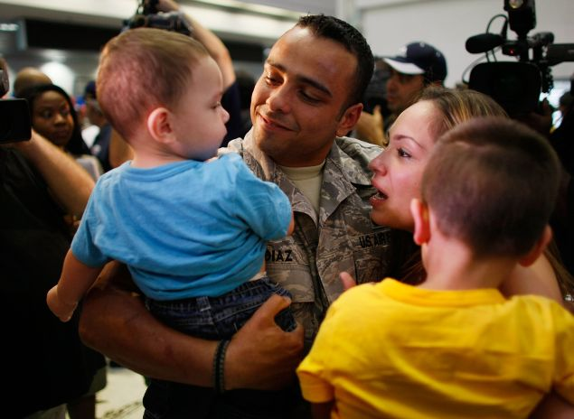 MIAMI - AUGUST 13: U.S. Air Force E-4 Senior Airman Francisco Diaz (2L) from the 482nd Security Forces Squadron at Homestead Air Reserve Base greets his fiancee Jacqueline Vazquez (2R) and sons Haisan Diaz (L), 1, and Julian Diaz, 3, as he arrives home after a six-month deployment to Iraq at the Miami International Airport August 13, 2008 in Miami, Florida.