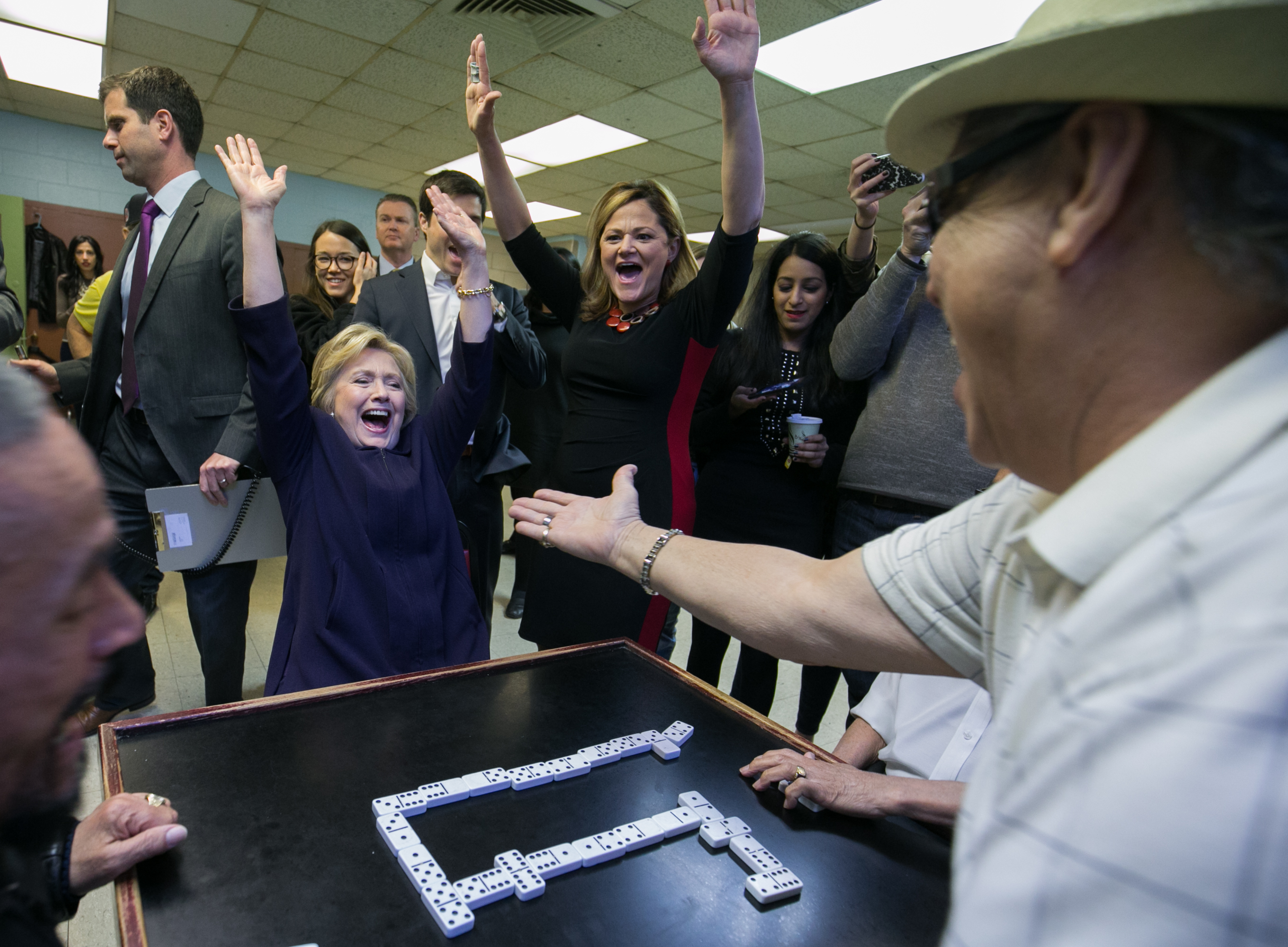 Hillary Clinton and Melissa Mark-Viverito cheer after the candidate wins a game of dominoes in an East Harlem housing project.