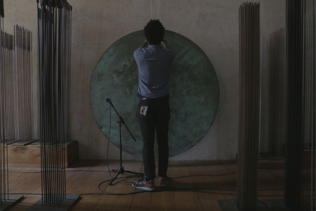 "Robert Aiki Aubrey Lowe performs on a gong in the Bertoia barn as part of a 2016 project titled ""We Echo Now His Love."""