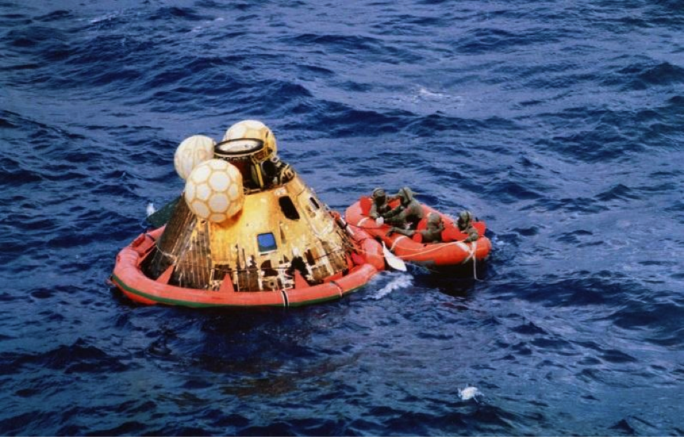 Apollo 11 crewmen await pickup by helicopter following splashdown on July 24, 1969.