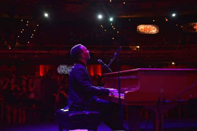 John Legend performing on stage at the Apollo Theater